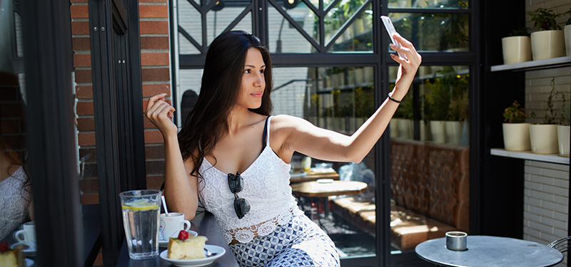 Charming girl taking picture of herself