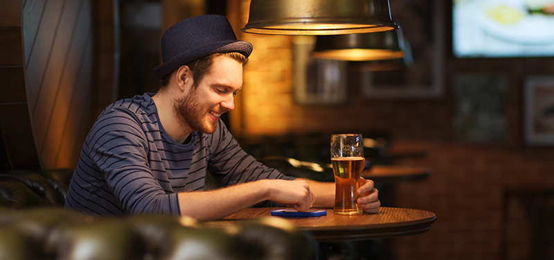 Man with smartphone and beer texting
